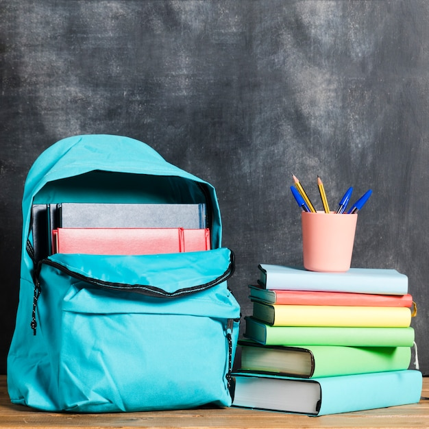 Backpack with books and pens Free Photo