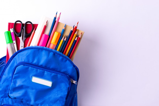 Backpack with different colorful stationery on white table. back to school concept. Premium Photo