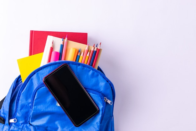 Backpack with different colorful stationery with smart phone on white table background Premium Photo