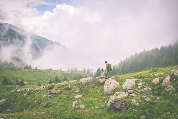 Backpacker standing on mountain footpath, toned Premium Photo