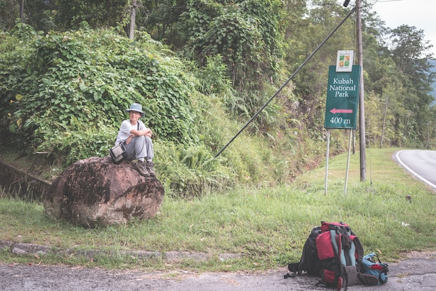 Backpacker waiting for hitchhike on the road for kubah national park, sarawak, borneo, malaysia. Premium Photo