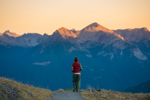 Backpacker walking on hiking trail in the mountain. summer adventures on the alps Premium Photo
