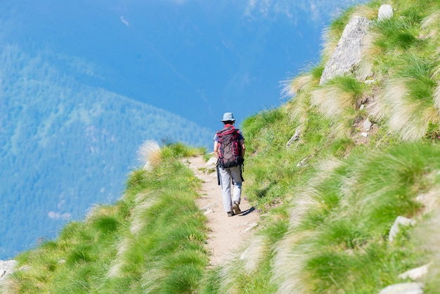 Backpacker walking on hiking trail in the mountain. summer adventures on the alps. Premium Photo