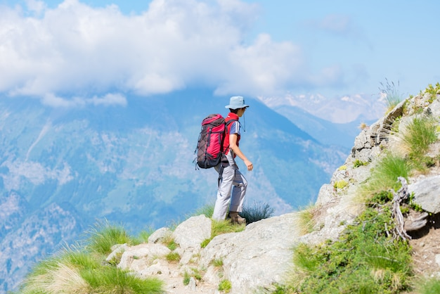 Backpacker walking on hiking trail in the mountains. summer adventures on the alps. Premium Photo