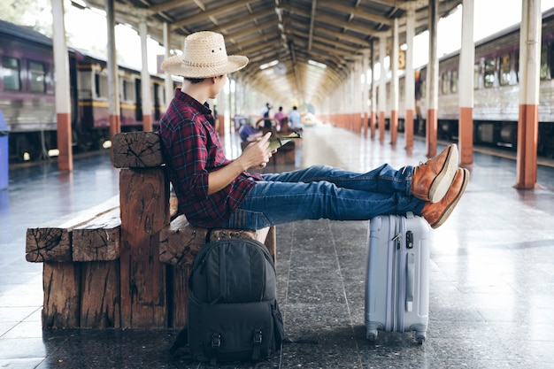 Backpackers are sitting to check the travel details with his map while waiting for the train to arrive at the train station Premium Photo
