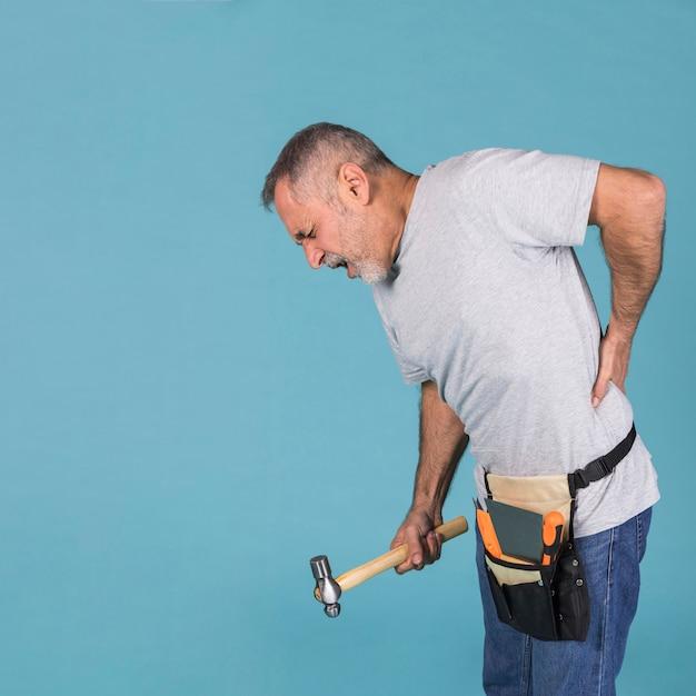 Разнорабочий, страдающий от backpain держит молоток стоя на синем фоне Бесплатные Фотографии