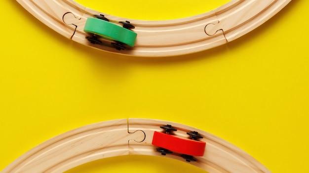 Рамка игрушек детей на желтом backround, игрушечной деревянной железной дороге и поезде. вид сверху. flatlay. скопируйте место для текста Premium Фотографии
