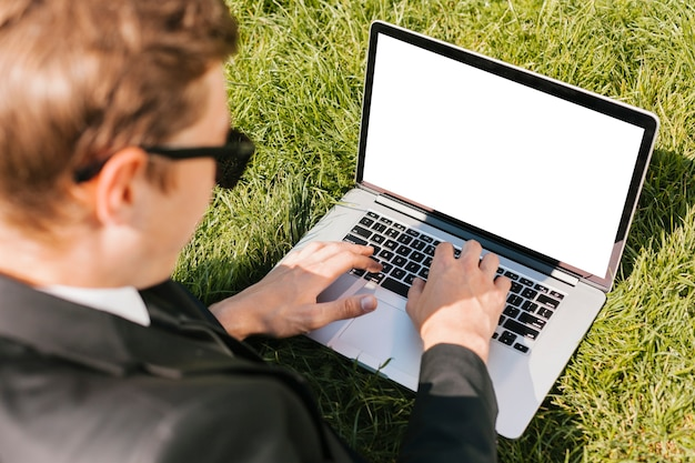 Backview business man using laptop on green grass Free Photo