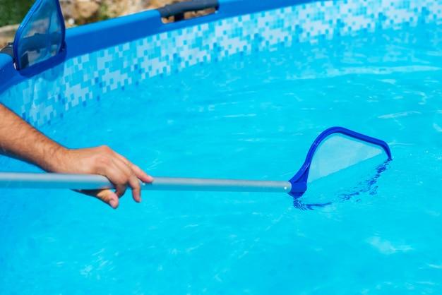 Backyard garden swimming pool cleaning close up Premium Photo
