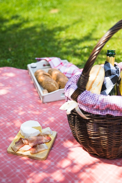 Bacon and cheese on chopping board over the cloth with picnic basket Free Photo