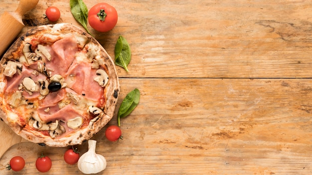 Bacon and mushroom pizza with fresh vegetables over textured wooden desk Free Photo