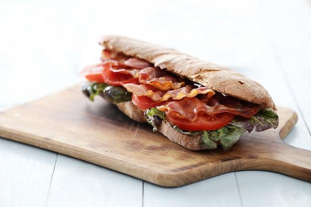 Bacon sandwich on wooden cutting board Free Photo