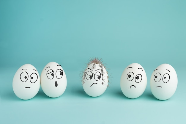 Bad character concept. prickly egg. five white eggs with drawn faces Premium Photo