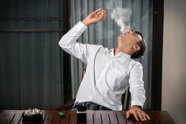 Плохие привычки. портрет парня, сидящего за столом, на котором стоит пепельница, полная сигарет, зажигалка с сигаретой в руке, выдувающий дым, который был отброшен назад. никотин. Premium Фотографии