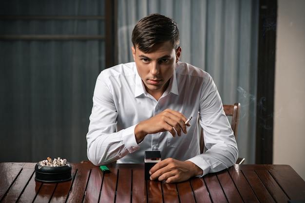 Плохие привычки. портрет парня, сидящего за столом, на котором стоит пепельница, полная сигарет Premium Фотографии