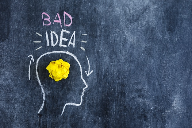 Bad idea text over the head with crumpled yellow paper in head drawn on chalkboard Free Photo