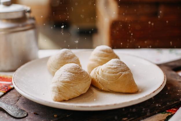昼間は茶色の木製の机の上の白いプレートの内側に粉砂糖を入れたおいしいミンチナッツの甘いバダンブラの有名な甘いもの 無料写真