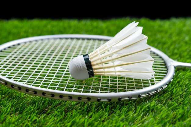 Badminton ball and racquet on grass in black background Premium Photo