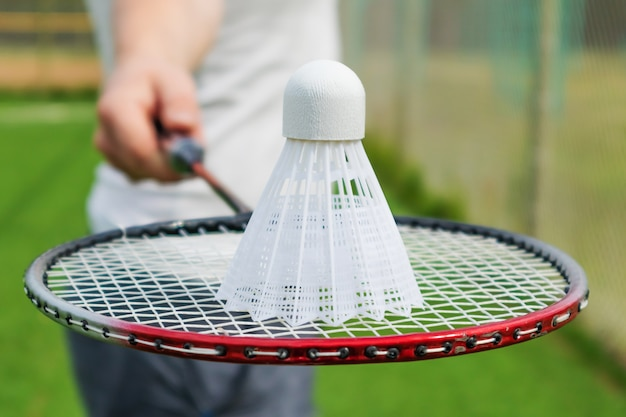 Badminton racket in the hand of a man in a white t-shirt. Premium Photo