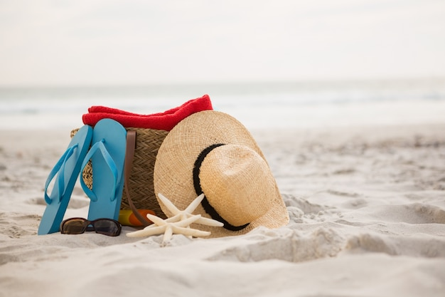 Bag and beach accessories kept on sand Free Photo