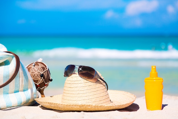Bag, maracas, straw hat with sunglasses and sunscreen lotion bottle on white sand Premium Photo