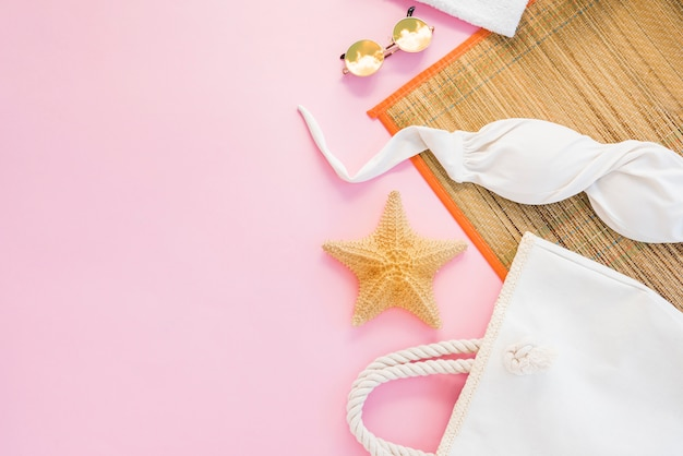 Bag near sunglasses and swimsuit among mat Premium Photo