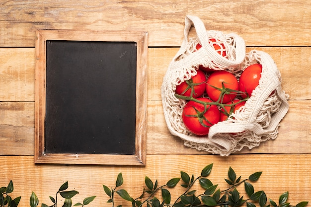 Bag of tomatoes next to empty chalkboard Free Photo
