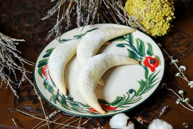 Бублики грецкие орехи тесто сахарная пудра вид сбоку Бесплатные Фотографии