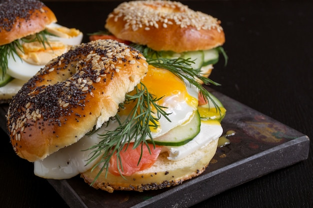 Bagels with egg and cucumber on black background. Premium Photo