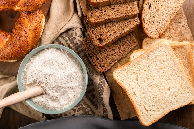 Bagels with slices of bread and bowl of flour Free Photo