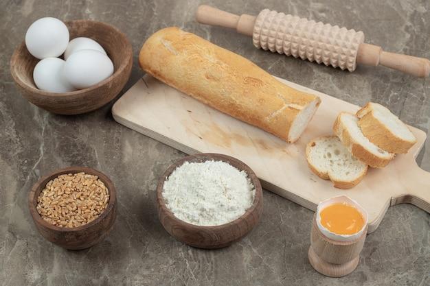 Багет, яйца, мука, ячмень и скалка на мраморной поверхности. фото высокого качества Бесплатные Фотографии