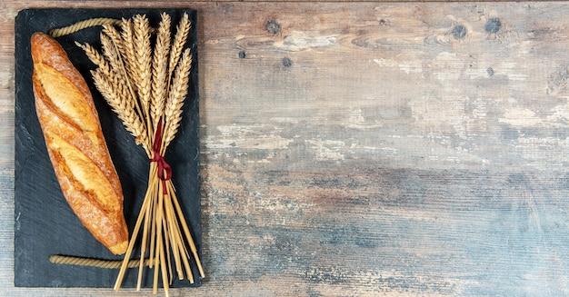 バゲットまたはフランスパンといくつかの小麦の穂 Premium写真