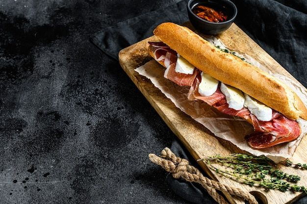 Baguette sandwich with jamon ham serrano, paleta iberica, camembert cheese on the cutting board Premium Photo