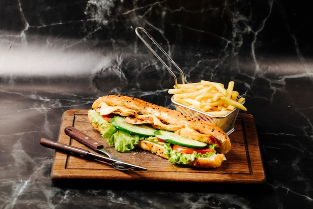 Baguette sandwich with mixed ingredients and french fries on a wooden board. Free Photo
