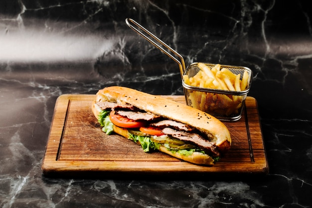 Baguette sandwich with mixed ingredients and french fries. Free Photo