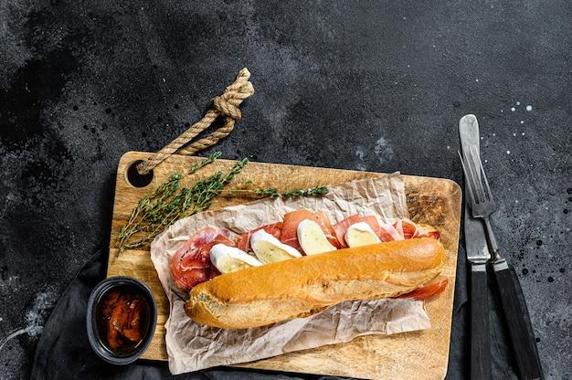 Baguette sandwich with prosciutto ham, camembert cheese on a cutting board Premium Photo