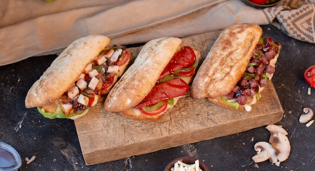 Baguette sandwiches with chicken, meat, sausage and vegetables, top view Free Photo