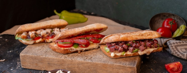 Baguette sandwiches with chicken, meat, sausage and vegetables Free Photo