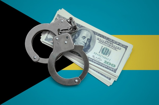 Bahamas flag  with handcuffs and a bundle of dollars. currency corruption in the country. financial crimes Premium Photo
