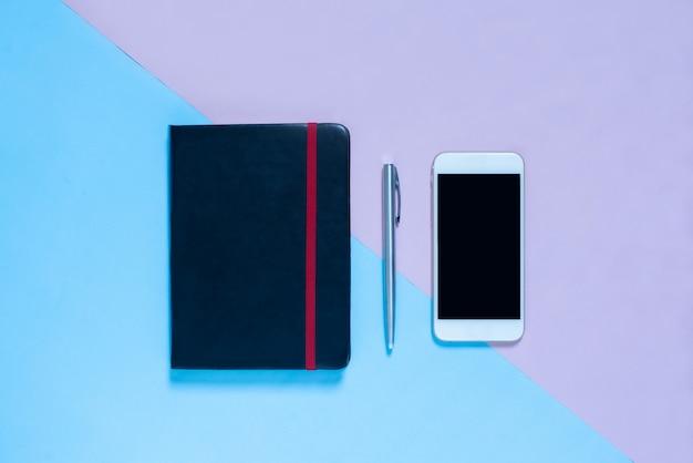 ノートブック、青とピンクのパステルカラーbakcgroundのペンのトップビュー Premium写真