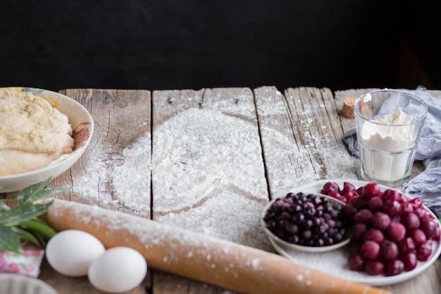 ハートの形をしたフルーツケーキを焼きます。おいしい自家製ケーキは自分で作ってください。料理。 3月8日。3月8日のグリーティングカード。女性の休日。バレンタイン・デー Premium写真