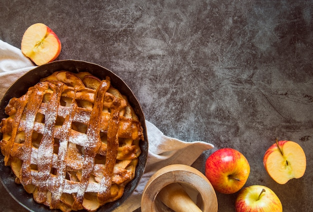 Baked apple pie on wooden table with fruit Free Photo