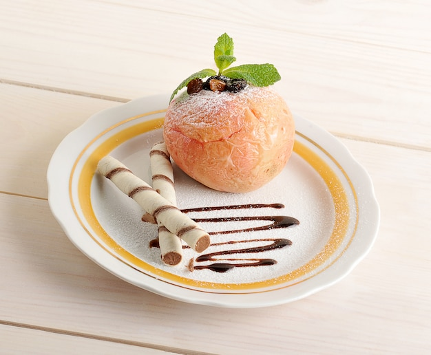 Baked apple with wafer rolls on a plate with chocolate and powdered sugar Premium Photo
