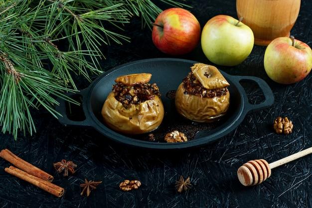 ナッツとドライフルーツを添えた焼きりんご。お正月とクリスマスのデザート Premium写真