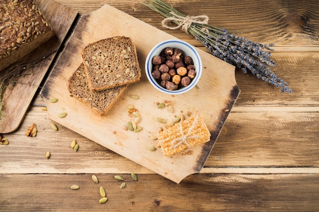 Baked bread and energy bar on chopping board over the table Free Photo