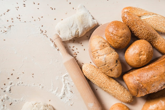 Baked breads with dough and rolling pin on backdrop Free Photo