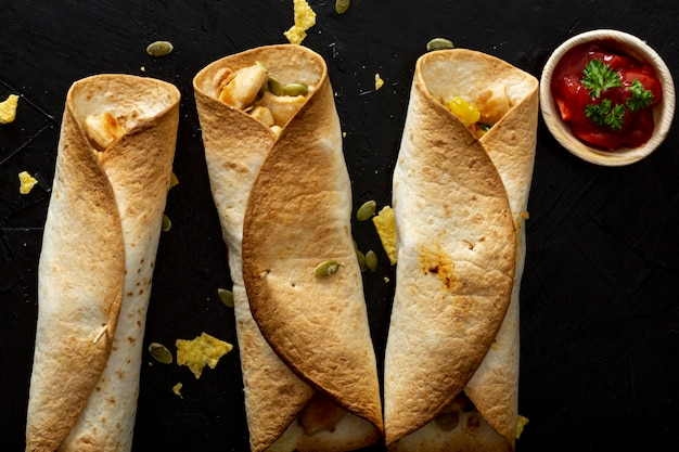 Baked burritos with chicken and red sauce in cup Free Photo
