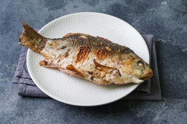 Baked carp fish on a plate. dark . copyspace. Photo | Premium Download