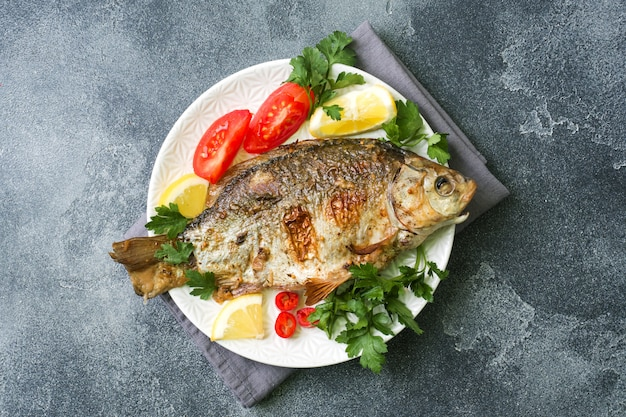 Baked carp fish with vegetables and spices on a plate on a dark table with a copy of space. Premium Photo
