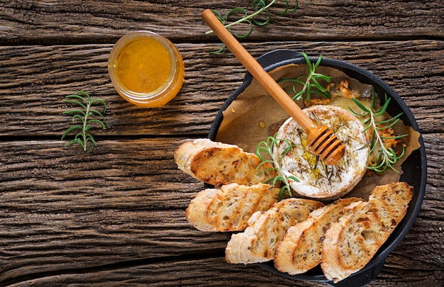Baked cheese camembert with rosemary and honey. tasty food. top view. flat lay Free Photo